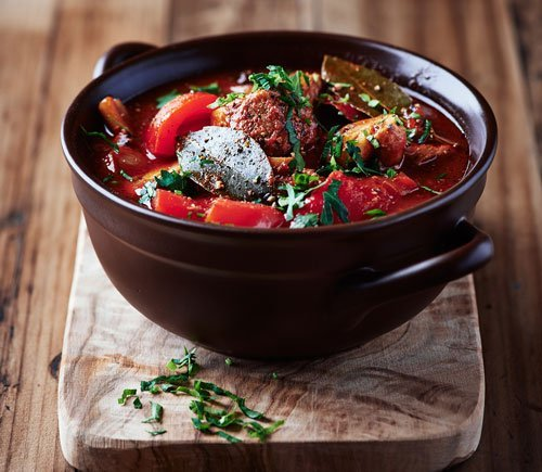 elk goulash in a black bowl on wood board