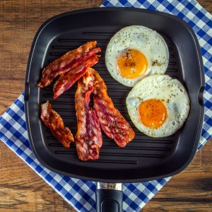 wild boar bacon and eggs in a fry pan