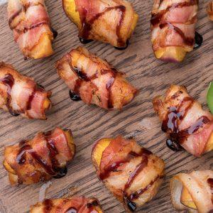 Le bacon grillé et enroulé autour d'un morceau de pêche