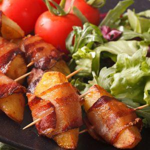 Enveloppez des quartiers de pommes de terre cuites au four de bacon de sanglier