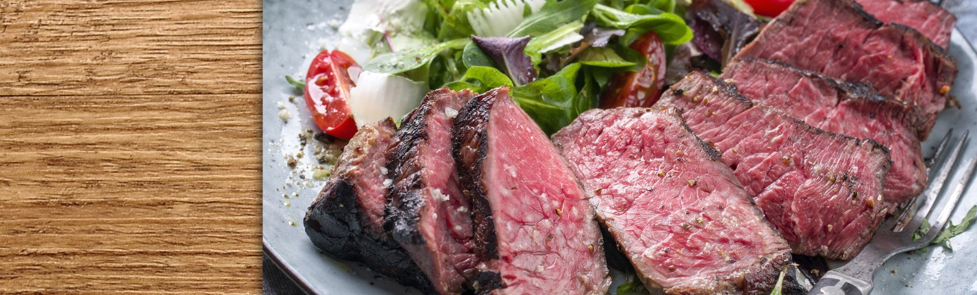 elk steaks sliced on a plate with salad
