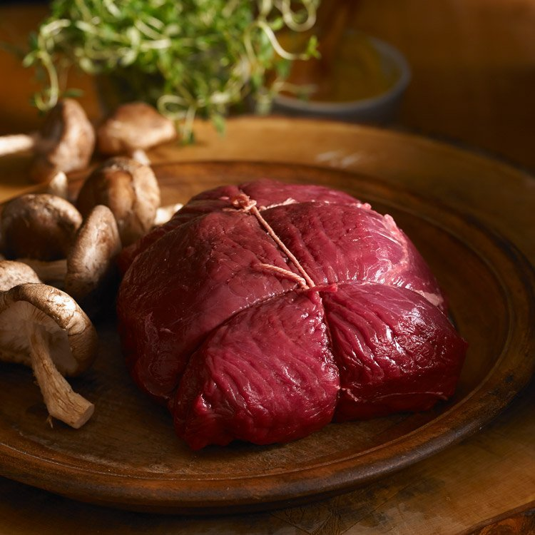 Raw elk roast with mushrooms on a brown plate