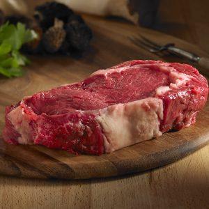 Bison rib eye steak raw on a wood board
