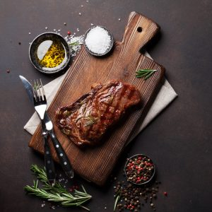 Bison Striploin steak on a cutting board with salt, olive oil and pepper