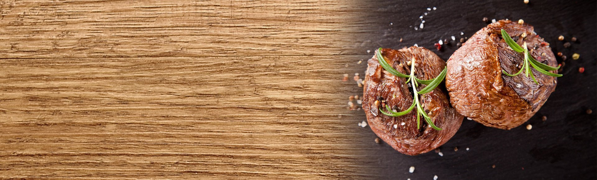2 juicy bison medallions on a black background with spices